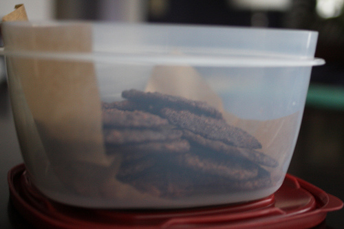 An image of thin chocolate cookies in a plastic container.