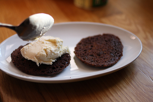 An image showing an oval white plate with thin chocolate cookies and one being ladled with ice cream.