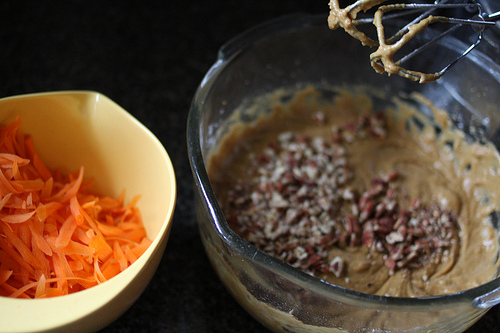 An image of two bowls sided by side, one filled with shredded carrots and the other with cake batter.