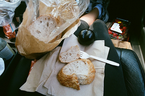 An image of a woman's lap with bread on it inside a car.
