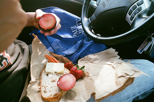 An image of a a person sitting on the driver's seat with bread, meat, cheese and fruit on his lap.