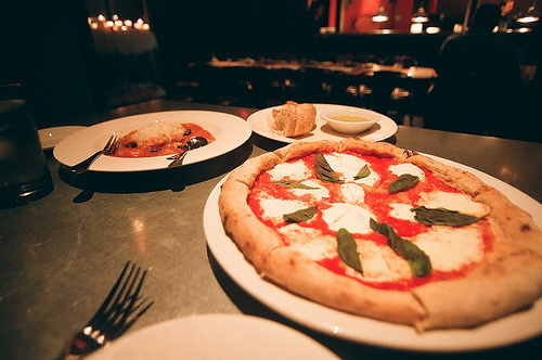 A beautiful Margherita pizza with that table set for two.