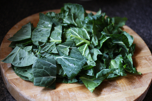 An image showing chopped collard greens on a wooden chopping board.