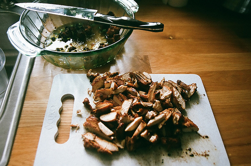 An image showing chopped chicken on a chopping board and a bowl and knife at the back.