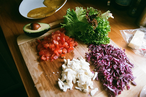 An image of a showing various diced vegetables on a chopping with a halved avocado and tacos at the back.