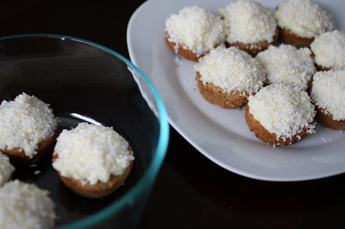 An image coconut cupcakes on a white plate and a few more on a clear glass bowl.