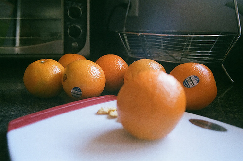 An image of whole ripe oranges on a counter.