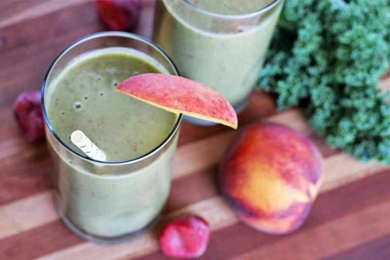 Two glasses of green smoothie with a white paper straw and a slice of peach on the rim, with a whole stone fruit, frozen berries, and a large leaf of green kale with curly edges, on a brown striped wood table.