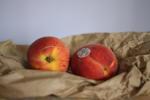 An image of two ripe peaches on a brown paper bag.