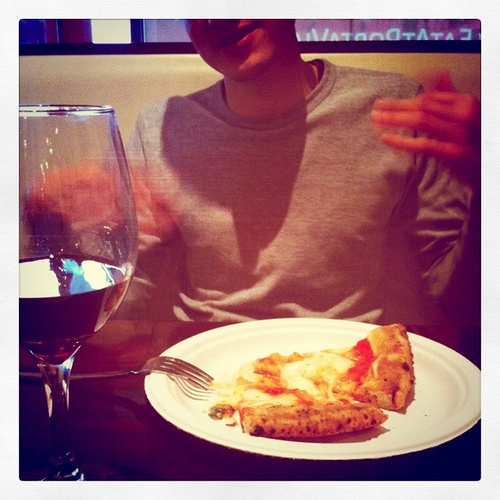 An image showing a man with a pizza in front of him and a glass of wine.