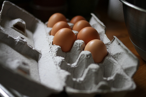 An image of a carton egg with seven whole eggs in it.