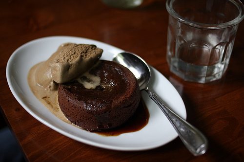 A white plate with small chocolate cake infused with coffee and a serving of ice cream on the side.