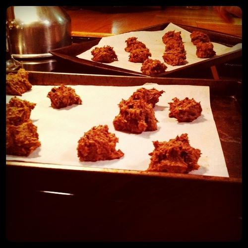 An image of two baking trays with chocolate buckwheat cookies.
