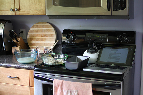 An image of a kitchen counter with a cooking stove and various kitchen utensils.