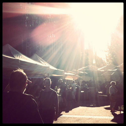 An image of the rays of sun streaming down tents and various food stalls.
