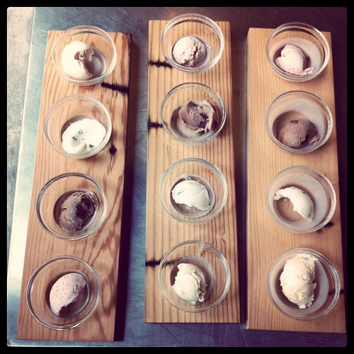 An image of various bowls of ice cream on top of board planks.