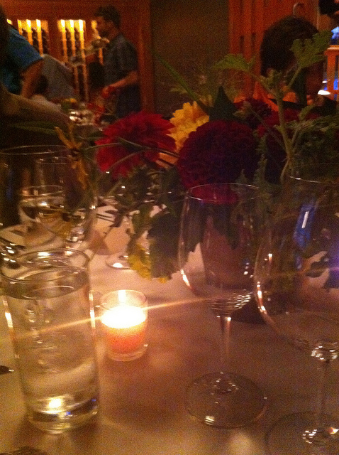 An image of a table with fresh flowers at the center and a single lit candle.