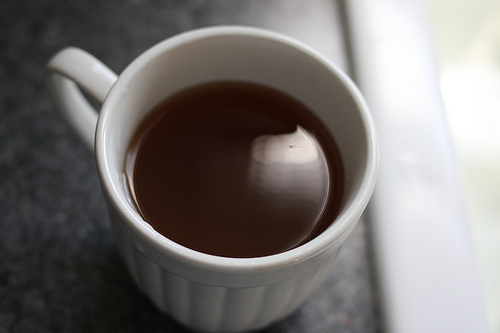 A top view image of a white cup filled with warm tea.