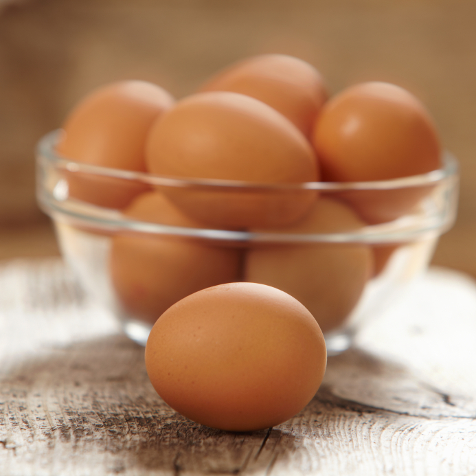 An image of a single brown egg in front and a bowl filled with more brown eggs.