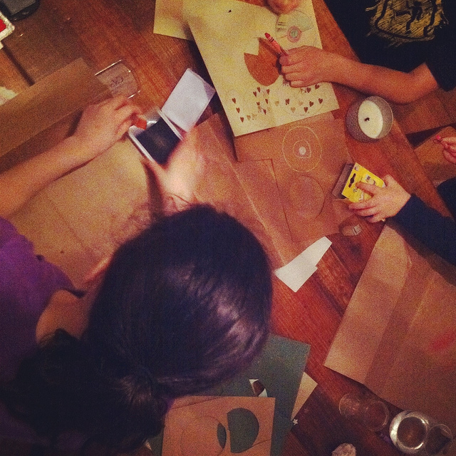 An image of a table with people surrounding it and creating Christmas decors and wrapping gifts.