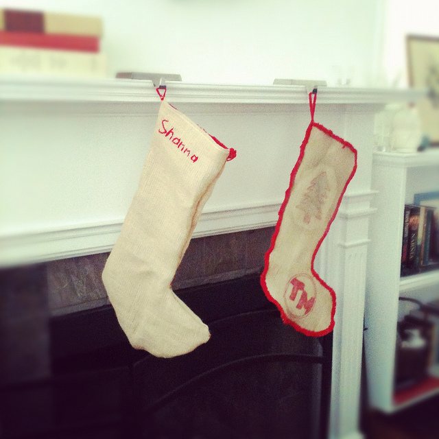 An image of two Christmas stocking hanging by a fireplace.