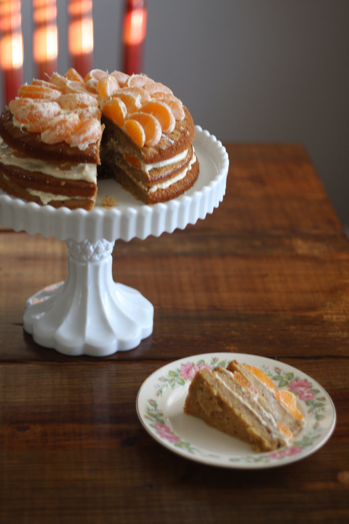 An image of Satsuma layer cake on a cake tray with a small slice on a plate beside it.
