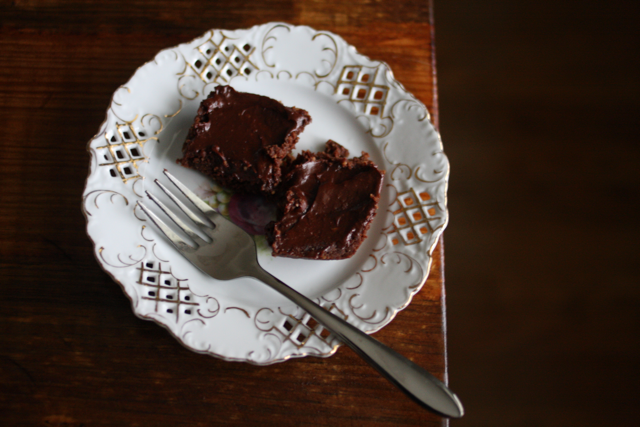 A top view image of a delicious brownies on an elegant white plate with a fork beside it.