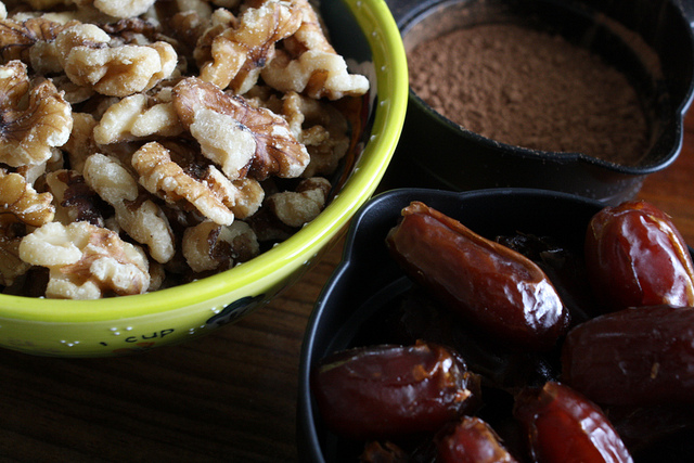 A close up image of dates and nuts on different containers.