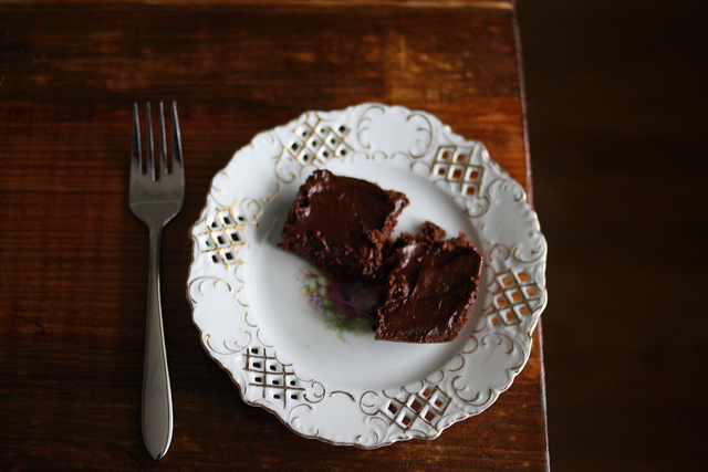 An image of brownies on an ornately designed plate and a piece of fork beside it.