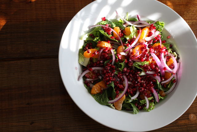 A top view image of a colorful and refreshing salad on a white plate.