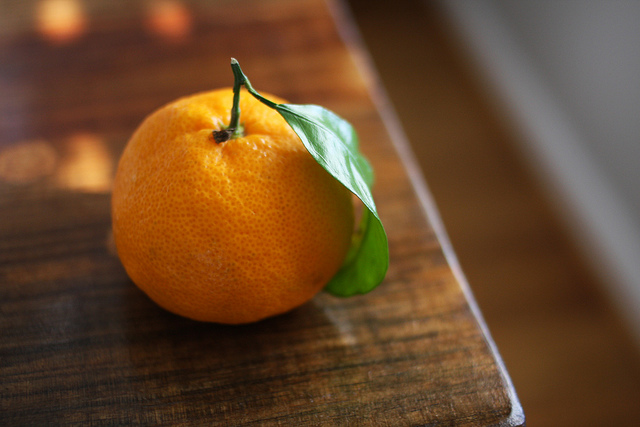 An image of a ripe orange near the edge of a table.