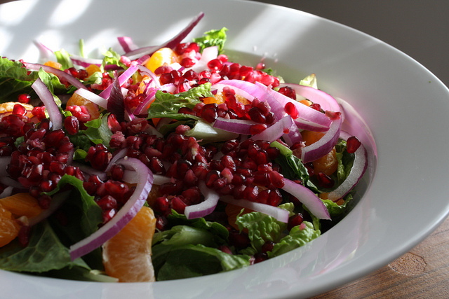 A close up image of a delicious salad with pomegranates, satsuma, and red onions.