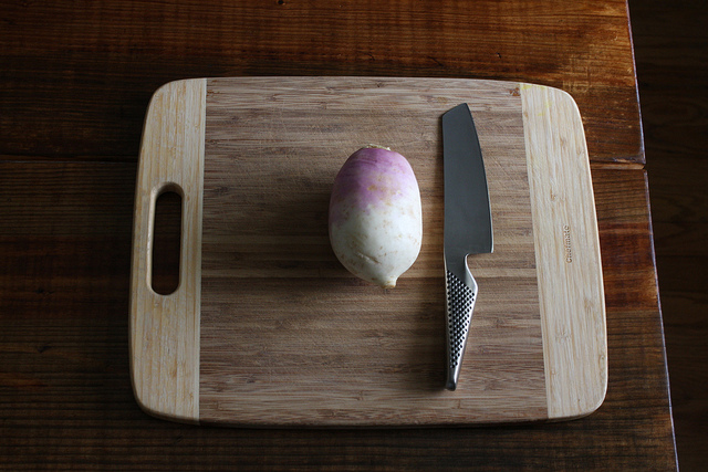 An image of a root vegetable on a chopping board with a knife beside it.