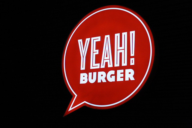 An image of a led signage of a burger joint against a dark background.