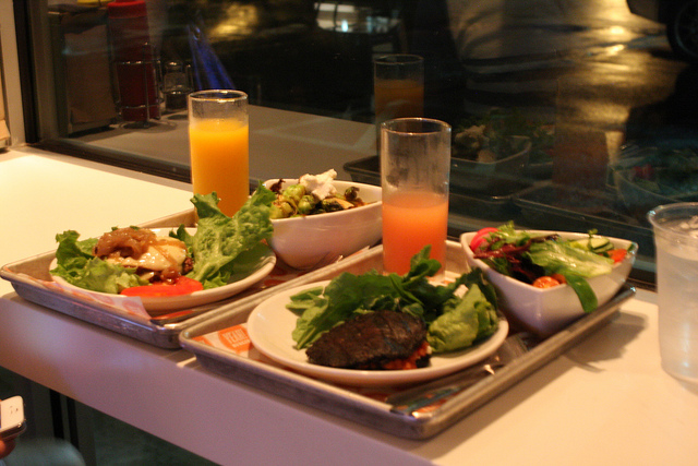 An image of two trays filled with salad, a glass of juice, and a bunless burger.