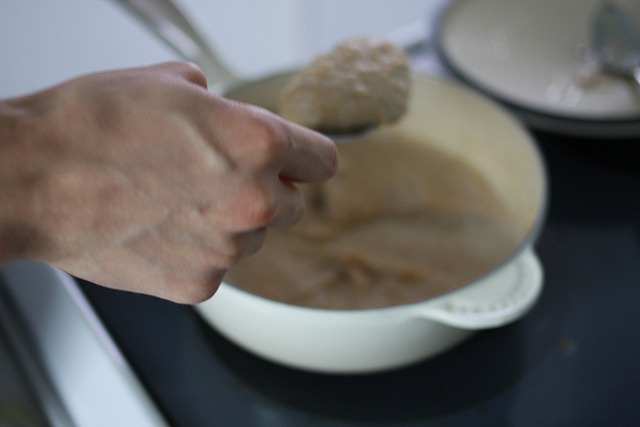 An image of a hand holding a spoon filled with amaranth porridge over a bowl.