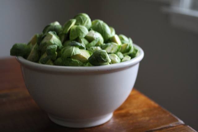 An image of a white bowl filled with fresh Brussels Sprouts.
