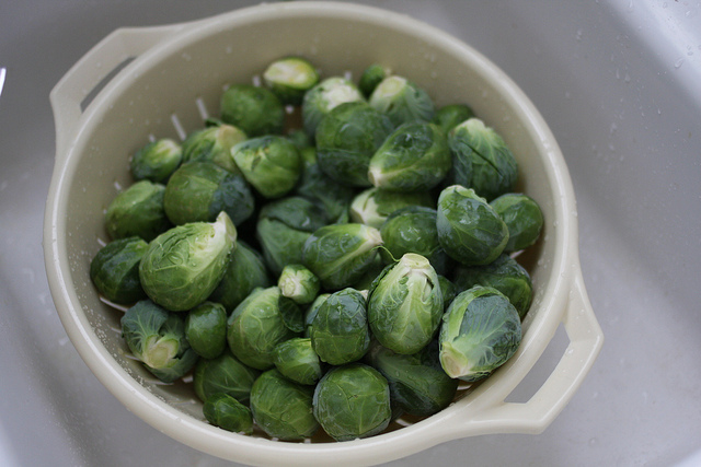 A top view image of fresh Brussels Sprouts in a white bowl.
