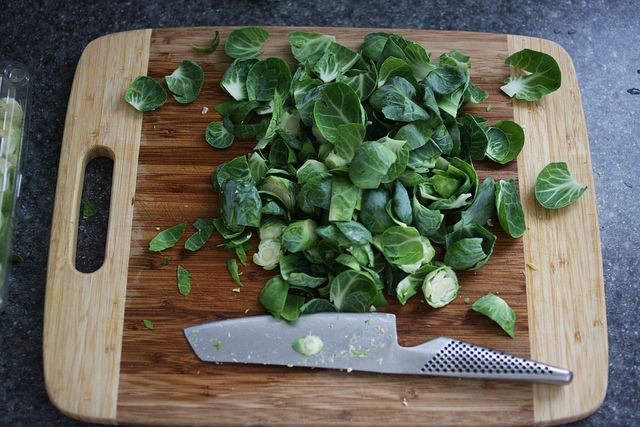 A chopping board with sliced Brussels Sprouts and a knife beside it.