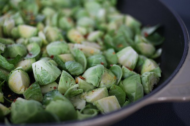 A close up image of sliced Brussels Sprouts in a skillet.