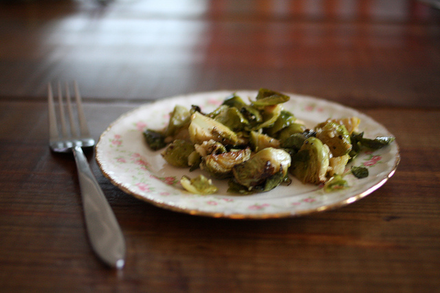 An image of a fork and a white plate filled with caramelized Brussels Sprouts.