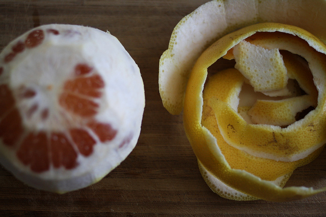 A top view image of a peeled grapefruit with its peelings beside it.