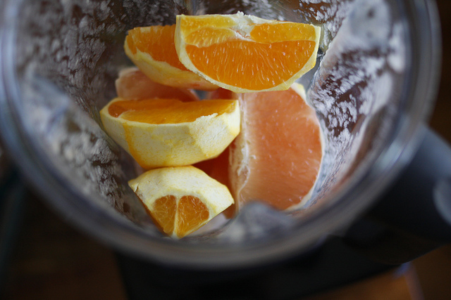 A top view image of grapefruit slices in a blender.