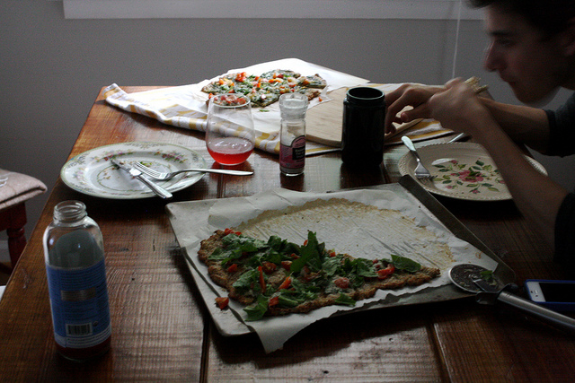 An image showing a man eating on a table and some empty plates and remaining pizza slices in front of him.