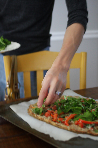 An image of a hand adding garnishes to a newly baked pizza.