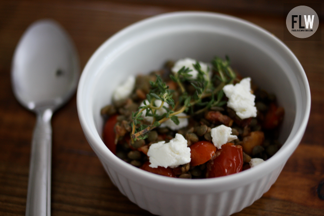 An image of a spoon and a white bowl filled with lentils, tomatoes, and cheese