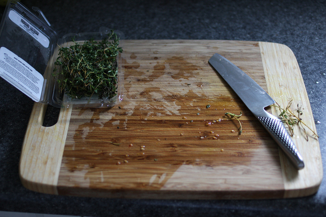 An image of a wooden chopping board with a knife on the right side and a sprig of thyme on the other side.