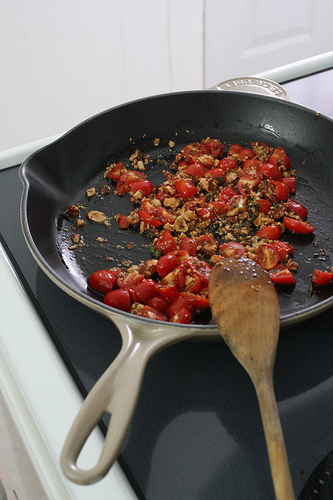 A top view image of a frying pan with tomatoes and lentils in it and a wooden spoon for stirring.