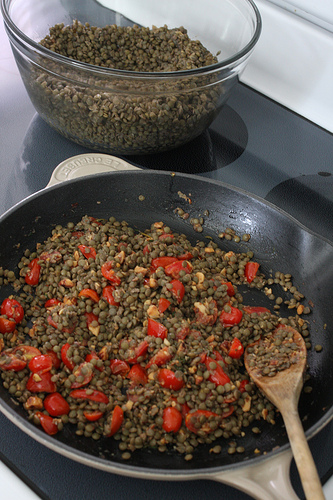 A close up image of a frying pan with lentils and tomatoes in it and a wooden spoon for stirring.