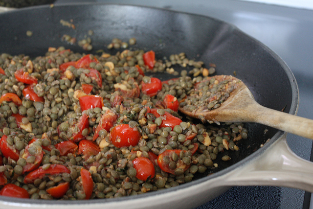 An image of tomatoes and lentils and a wooden spoon in a pan.